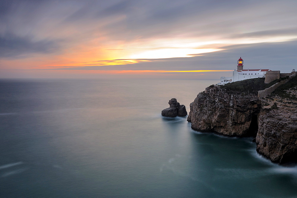 Dusk lights up the lighthouse overlooking the Atlantic Ocean, Cabo De Sao Vicente, Sagres, Algarve, Portugal, Europe