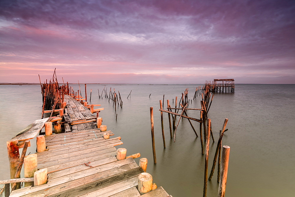 Pink sky at dawn on the Palafito Pier in the Carrasqueira Natural Reserve of Sado River Alcacer do Sal Setubal Portugal Europe