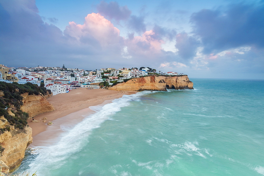 View of Carvoeiro village surrounded by sandy beach and turquoise sea at sunset Lagoa Municipality Algarve Portugal Europe