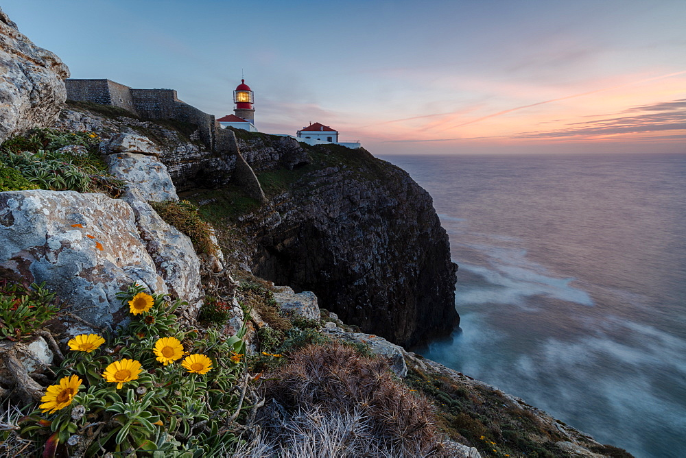 Pink sky at sunset and yellow flowers frame the lighthouse, Cabo De Sao Vicente, Sagres, Algarve, Portugal, Europe