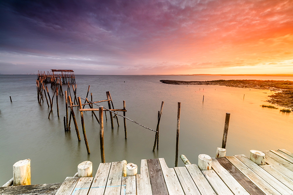 Fiery sky at dawn on the Palafito Pier in the Carrasqueira Natural Reserve of Sado River Alcacer do Sal Setubal Portugal Europe
