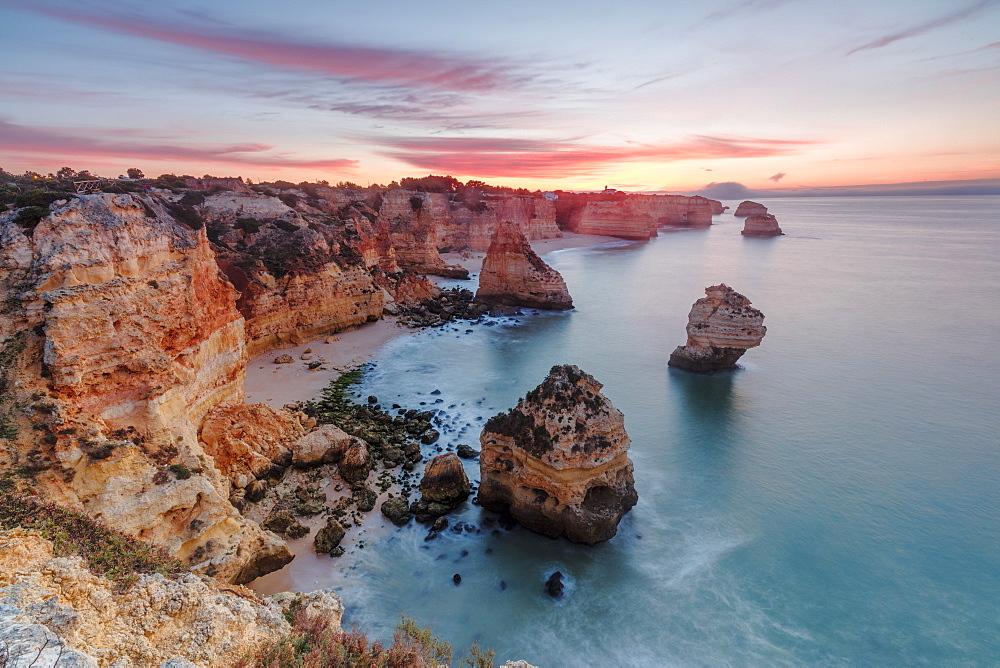 Sunrise on cliffs framed by turquoise water of the ocean Praia da Marinha Caramujeira Lagoa Municipality Algarve Portugal Europe - 1179-1921