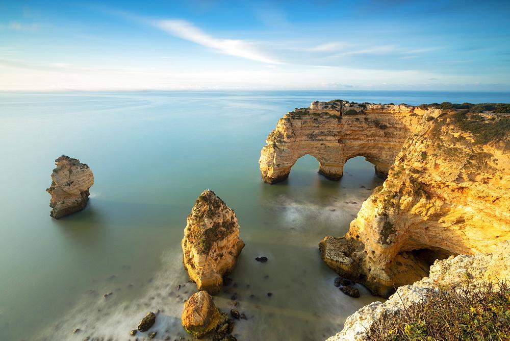 Sunrise on cliffs framed by turquoise water of the ocean Praia da Marinha Caramujeira Lagoa Municipality Algarve Portugal Europe - 1179-1923