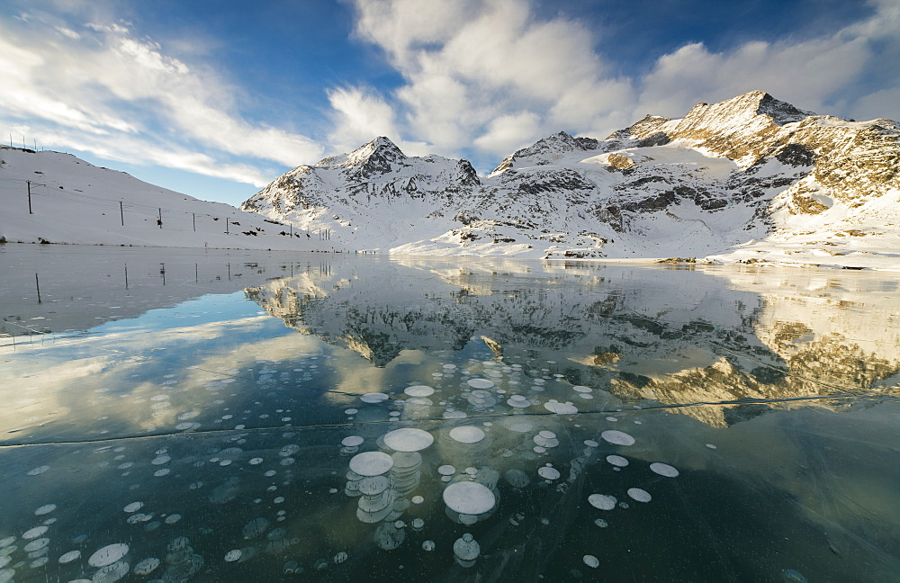 Ice bubbles frame the snowy peaks reflected in Lago Bianco, Bernina Pass, canton of Graubunden, Engadine, Switzerland, Europe