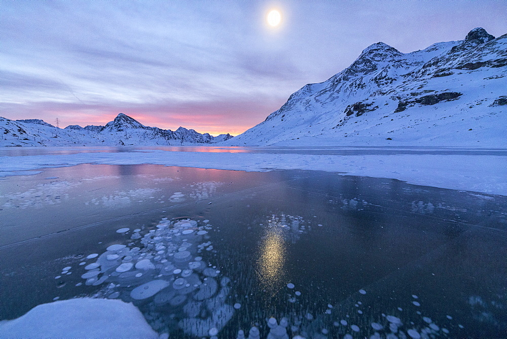 Ice bubbles frame the frozen Lago Bianco at dawn, Bernina Pass, canton of Graubunden, Engadine, Switzerland, Europe