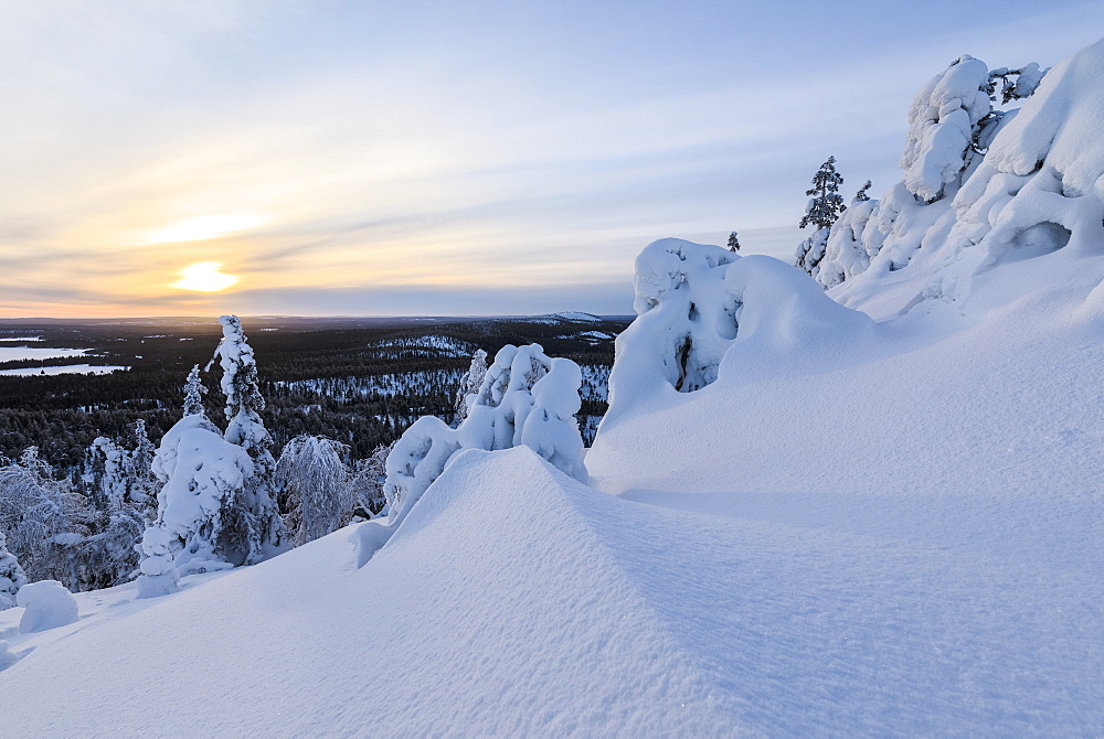 The sun frames the snowy landscape and woods in the cold arctic winter, Ruka, Kuusamo, Ostrobothnia region, Lapland, Finland, Europe