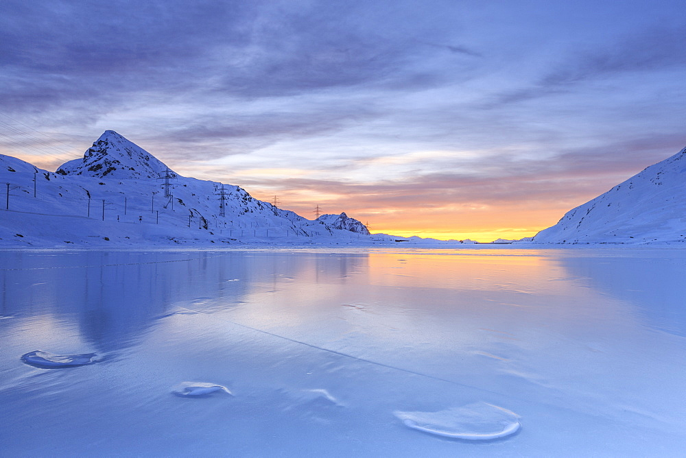 The colors of dawn invading the smooth surface of Lago Bianco exceptionally icy, Bernina Pass, Graubunden, Swiss Alps, Switzerland, Europe