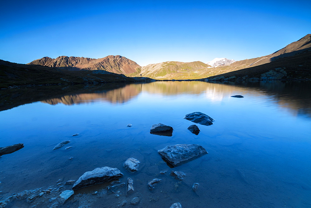 The rocky peaks reflected in Lake Umbrail at sunset, Stelvio Pass, Valtellina, Lombardy, Italy, Europe
