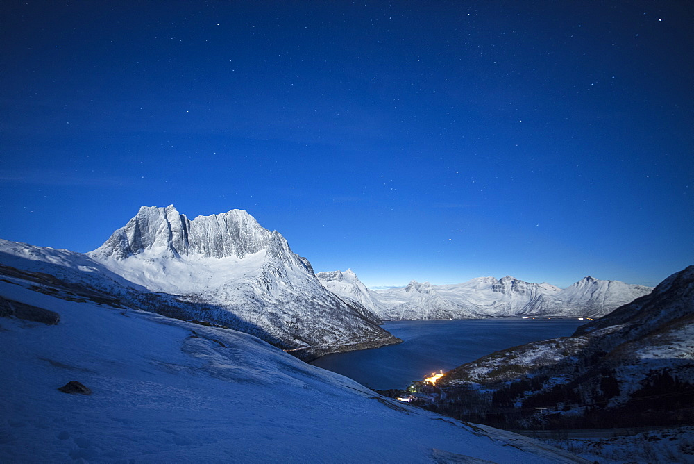 Stars of the polar night on the Senjahopen peak framed by frozen sea Senja Mefjordbotn Troms county Norway Europe