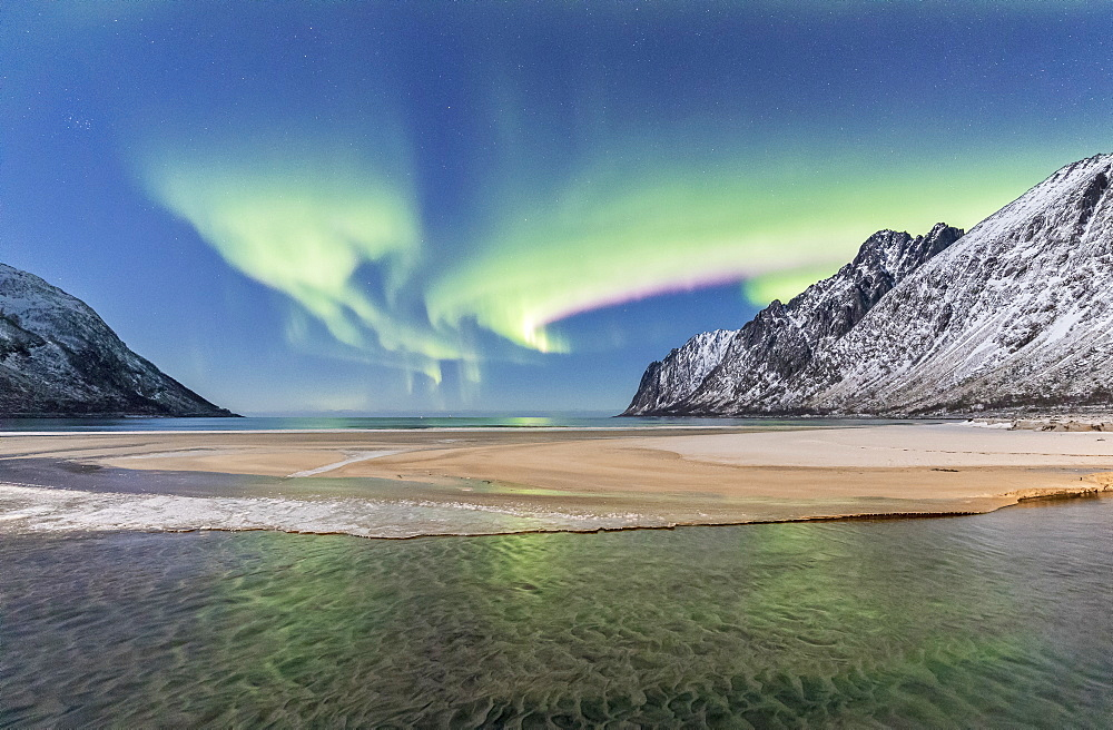 Green lights of Aurora Borealis reflected in the cold sea surrounded by snowy peaks Ersfjord Senja Tromsø Norway Europe