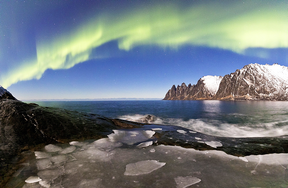 Panorama of frozen sea and rocky peaks illuminated by the Northern Lights Tungeneset Senja Tromsø Norway Europe