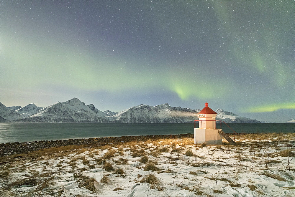 The Northern Lights and stars illuminate the lighthouse framed by icy sea Djupvik Lyngen Alps Tromsø Norway Europe