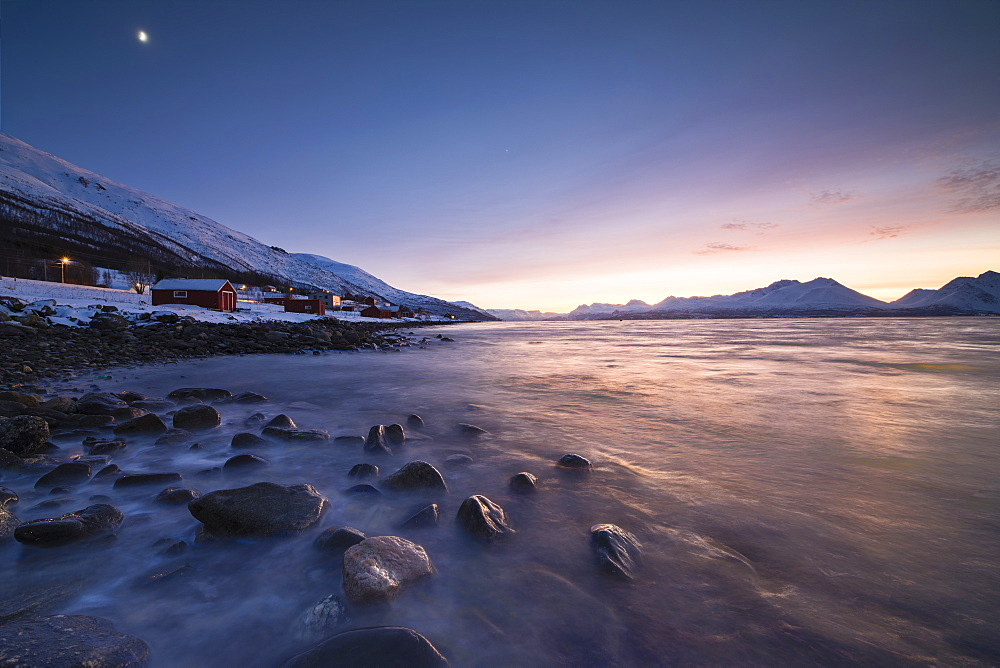 Fiery sky at sunset on typical Rorbu framed by snowy peaks and frozen sea Djupvik Lyngen Alps Tromsø Norway Europe