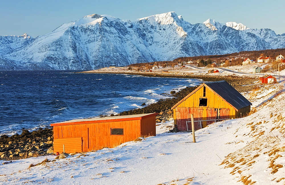 Typical wooden huts called Rorbu surrounded by waves of the cold sea and snowy peaks Djupvik Lyngen Alps Tromsø Norway Europe