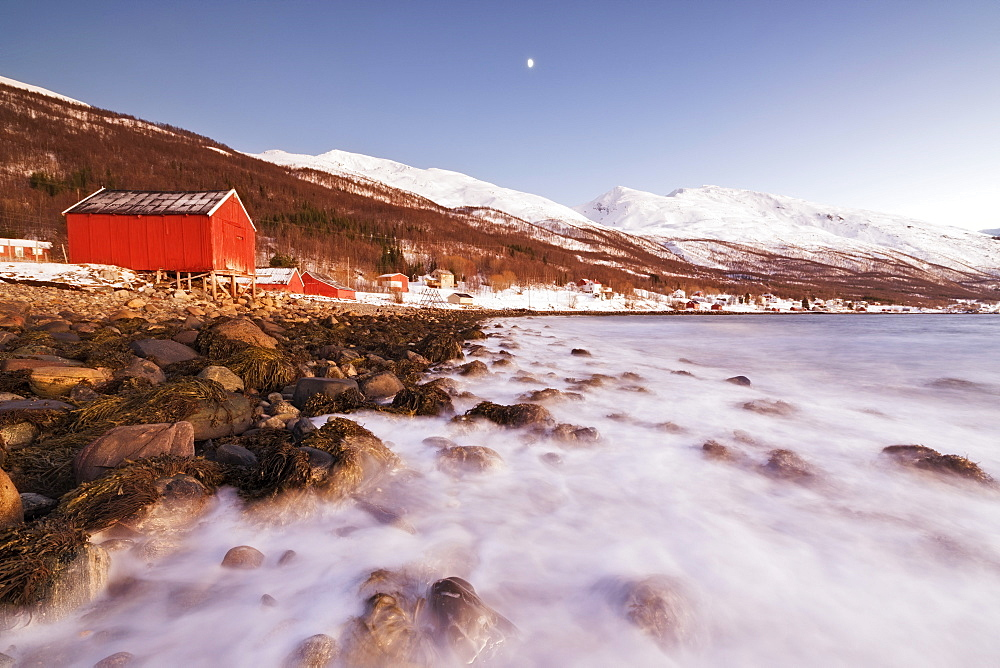 Waves of cold sea crashing on the rocks frame the typical wooden huts called Rorbu Djupvik Lyngen Alps Tromsø Norway Europe