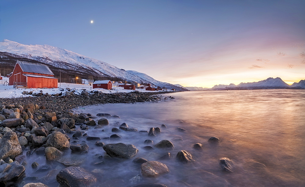 Panorama of typical wood huts called Rorbu framed by fiery sky at sunset and frozen sea Djupvik Lyngen Alps Tromsø Norway Europe