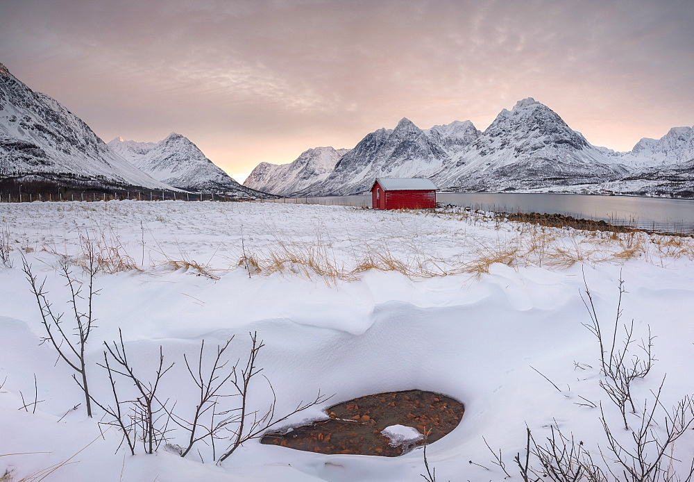 Panorama of pink sky at dawn on the wooden hut surrounded by frozen sea and snowy peaks, Svensby, Lyngen Alps, Troms, Norway, Scandinavia, Europe
