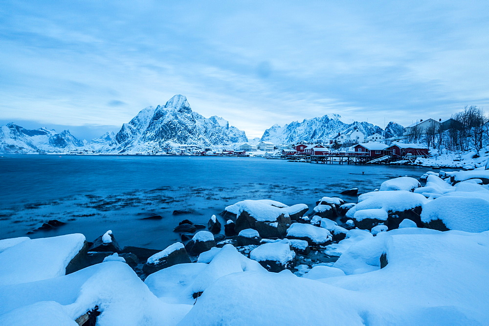 Blue hour in the bay of Reine, where for many months of the year the snow and cold force the residents to remain in their homes, Reine, Lofoten Islands, Arctic, Norway, Scandinavia, Europe