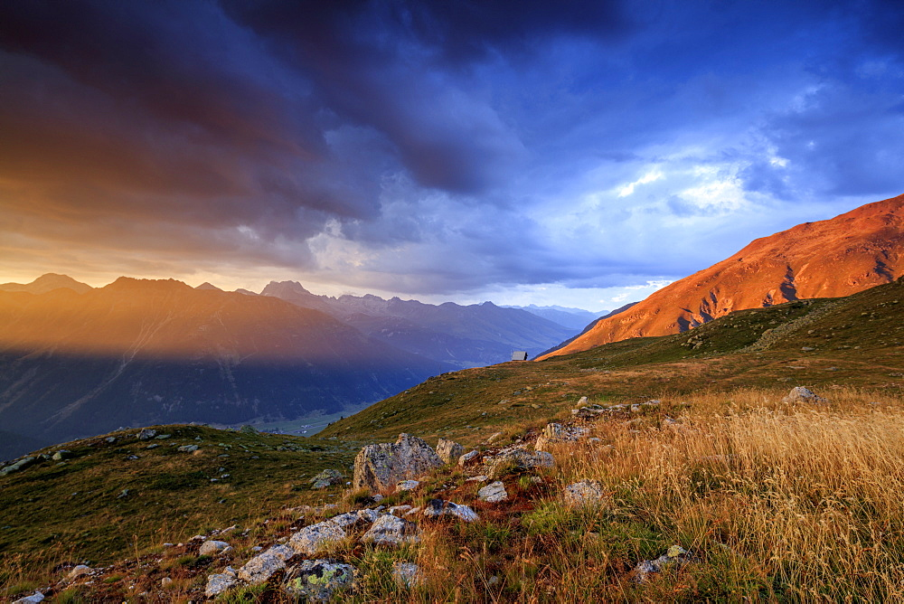Fiery sky and dark clouds on high peaks of Muottas Muragl at sunset St.Moritz Engadine Canton of Graubünden Switzerland Europe - 1179-2085