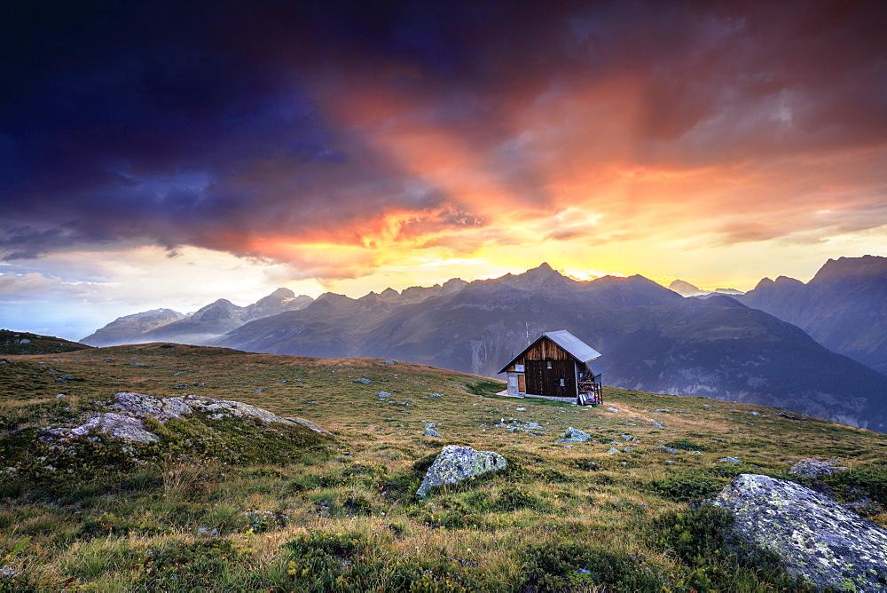 Wooden hut framed by fiery sky and clouds at sunset Muottas Muragl St.Moritz Engadine Canton of Graubünden Switzerland Europe - 1179-2088