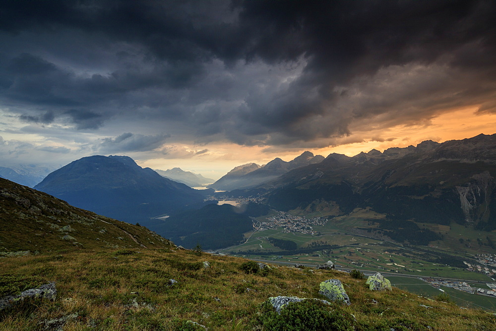 Dark clouds and sunset lights frame the rocky peaks of Muottas Muragl, St. Moritz, Canton of Graubunden, Engadine, Switzerland, Europe