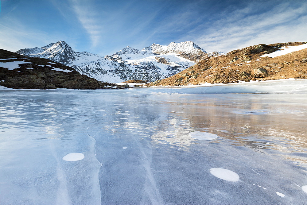 Blue sky on the frozen Lej Nair surrounded by snowy peaks, Bernina Pass, Canton of Graubunden, Engadine, Switzerland, Europe