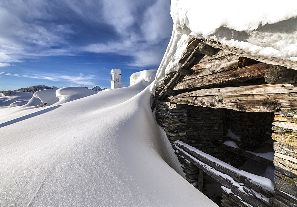 A mountain hut emerging from thick snow after a heavy snowfall in the Alpe Scima, Valchiavenna, Lombardy, Italy, Europe