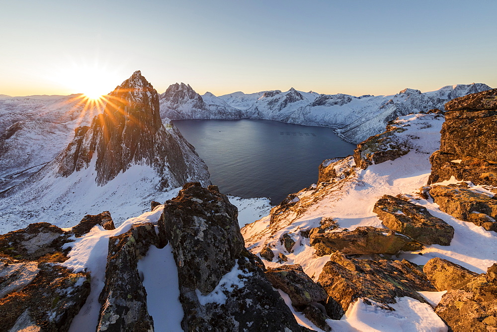 First light of sunrise on Mount Segla and Mefjorden framed by the frozen sea seen from peak Hesten, Senja, Troms, Norway, Scandinavia, Europe