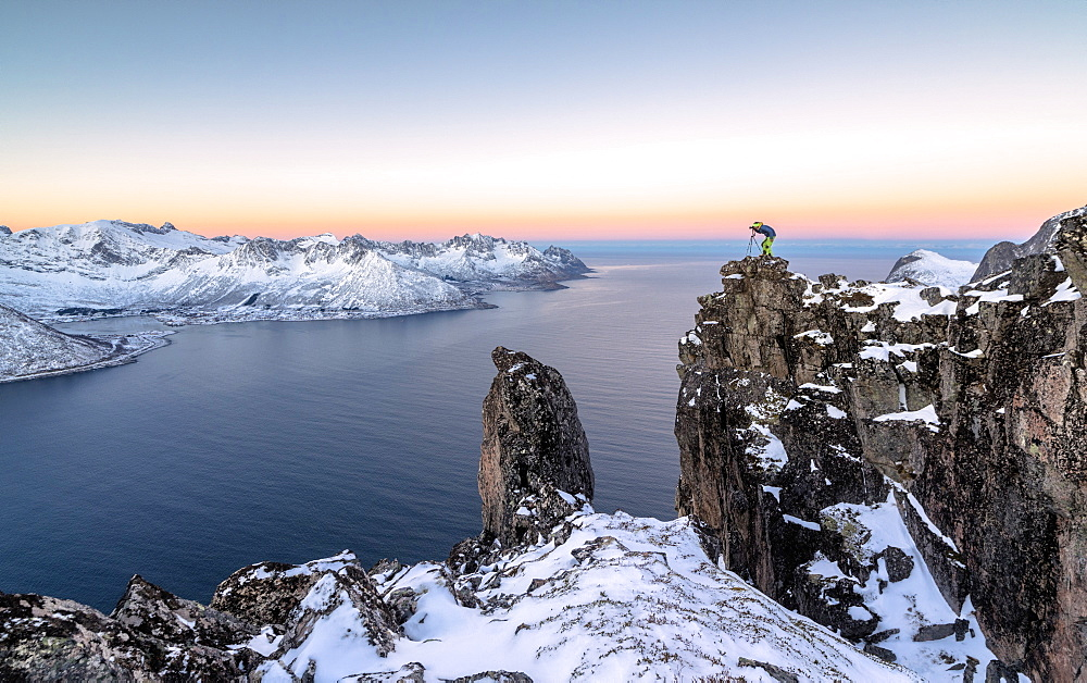 Photographer on the rocks on top of Mount Hesten admires the Mefjorden and the frozen sea at sunrise Senja Tromsø Norway Europe