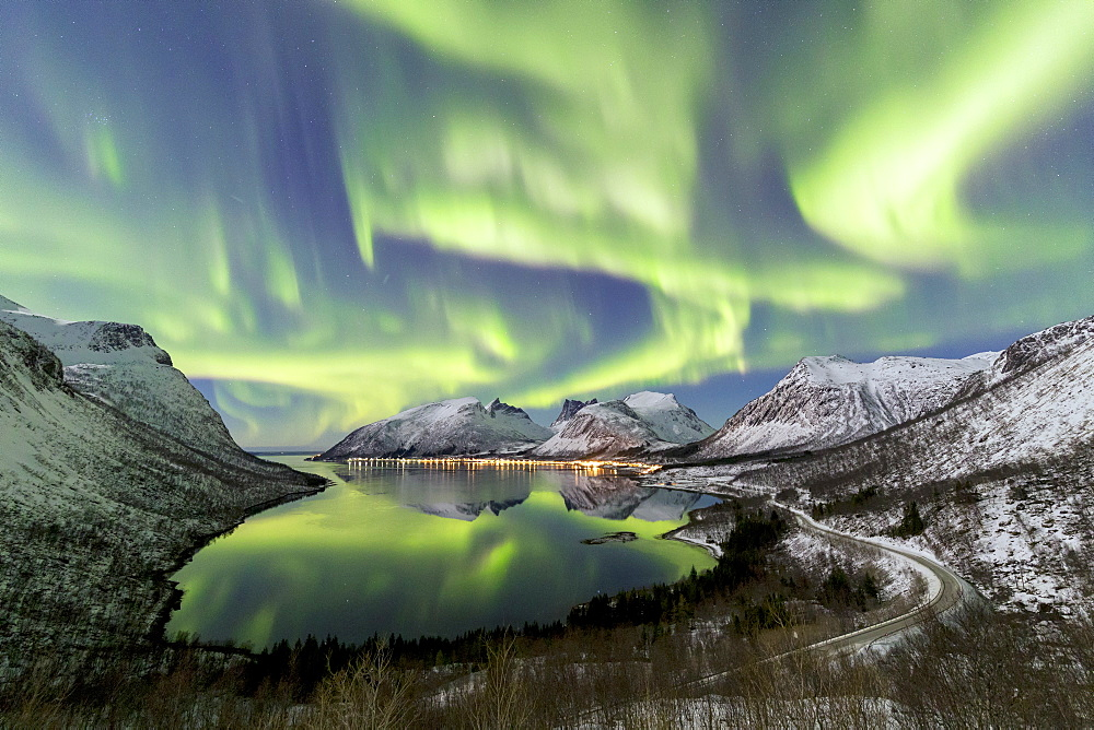 Northern lights and stars light up the snowy peaks reflected in the cold sea Bergsbotn Senja Tromsø Norway Europe