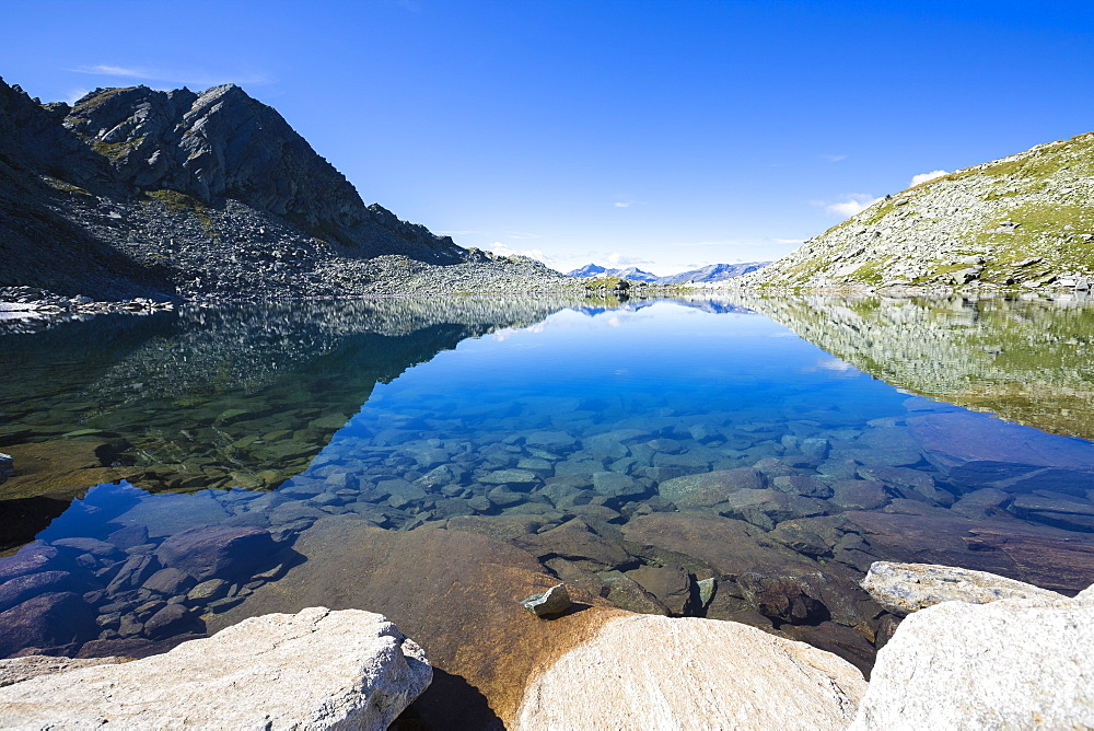 Blue sky and rocky peaks reflected in the blue Lago Nero, Chiavenna Valley, Valtellina, Lombardy, Italy, Europe