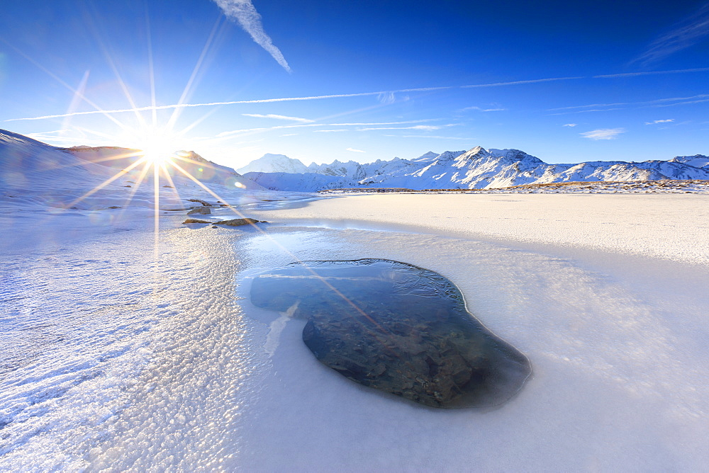 Rays of sun on the frozen Lake, Piz Umbrail framed by Mount Ortles in background, Braulio Valley, Valtellina, Lombardy, Italy, Europe
