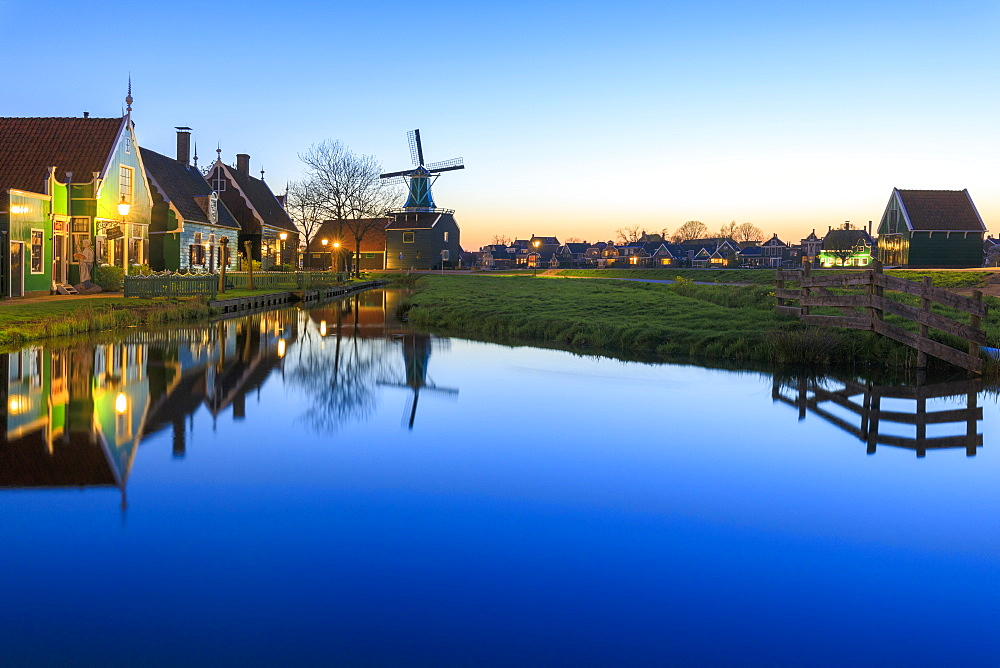 Blue lights at dusk on wooden houses and windmills of the typical village of Zaanse Schans, North Holland, The Netherlands, Europe