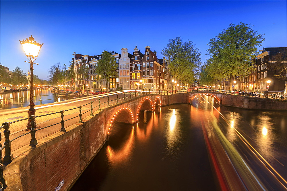 Dusk lights on typical buildings and bridges reflected in a typical canal, Amsterdam, Holland (The Netherlands), Europe