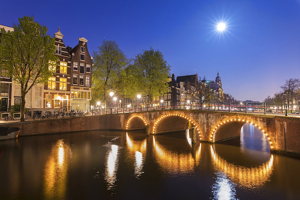 Dusk light on typical buildings and bridges reflected in a typical canal, Amsterdam, Holland (The Netherlands), Europe