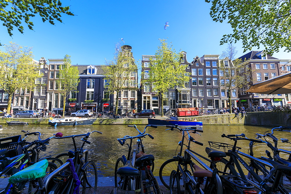 Bicycles parked on the banks of the river Amstel and typical houses, Amsterdam, Holland (The Netherlands), Europe