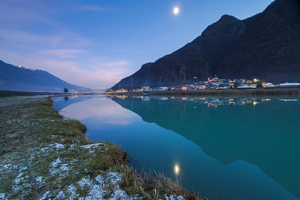 Last light of sunset on Adda River and the village of Sirta Forcola, province of Sondrio, Valtellina, Lombardy, Italy, Europe