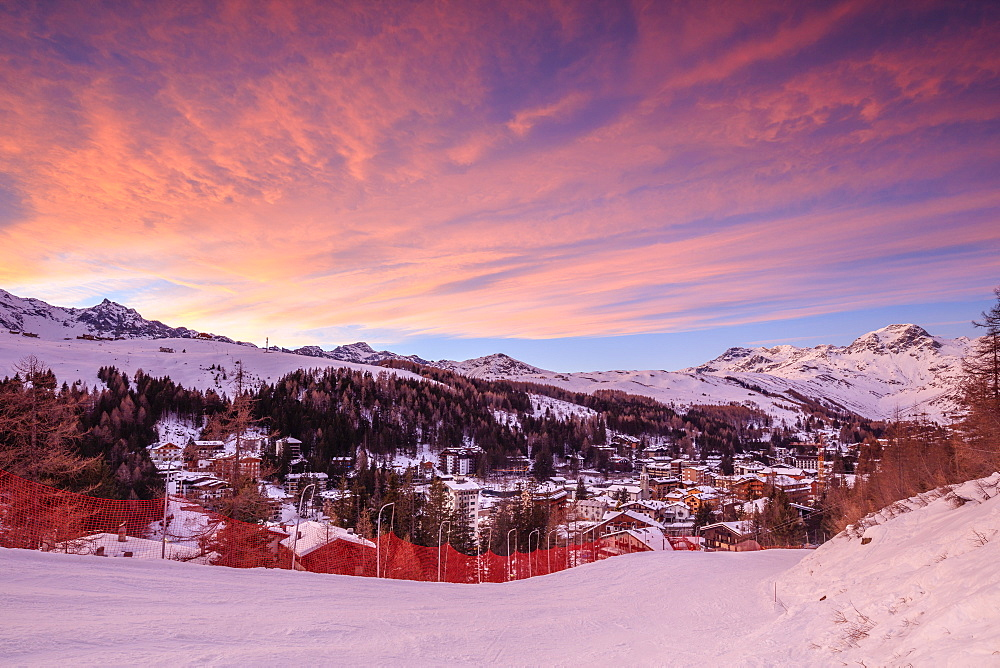 Pink clouds at sunset on the alpine village of Madesimo and the snowy ski slopes, Spluga Valley, Valtellina, Lombardy, Italy, Europe