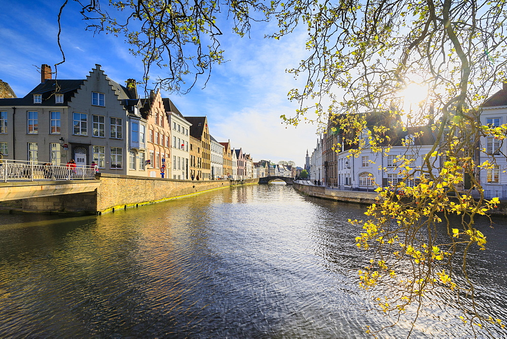 Spring sun on the medieval buildings of the city centre framed by bridges and typical canals, Bruges, West Flanders, Belgium, Europe