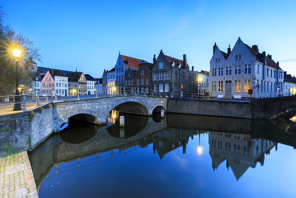 Dusk lights on the historic buildings of the city centre reflected in the typical canals, Bruges, West Flanders, Belgium, Europe