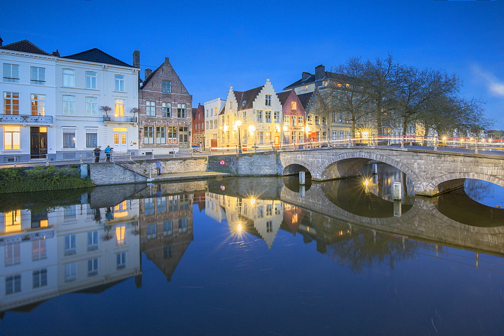 Dusk lights on the historic buildings of the city centre reflected in the typical canals Bruges West Flanders Belgium Europe