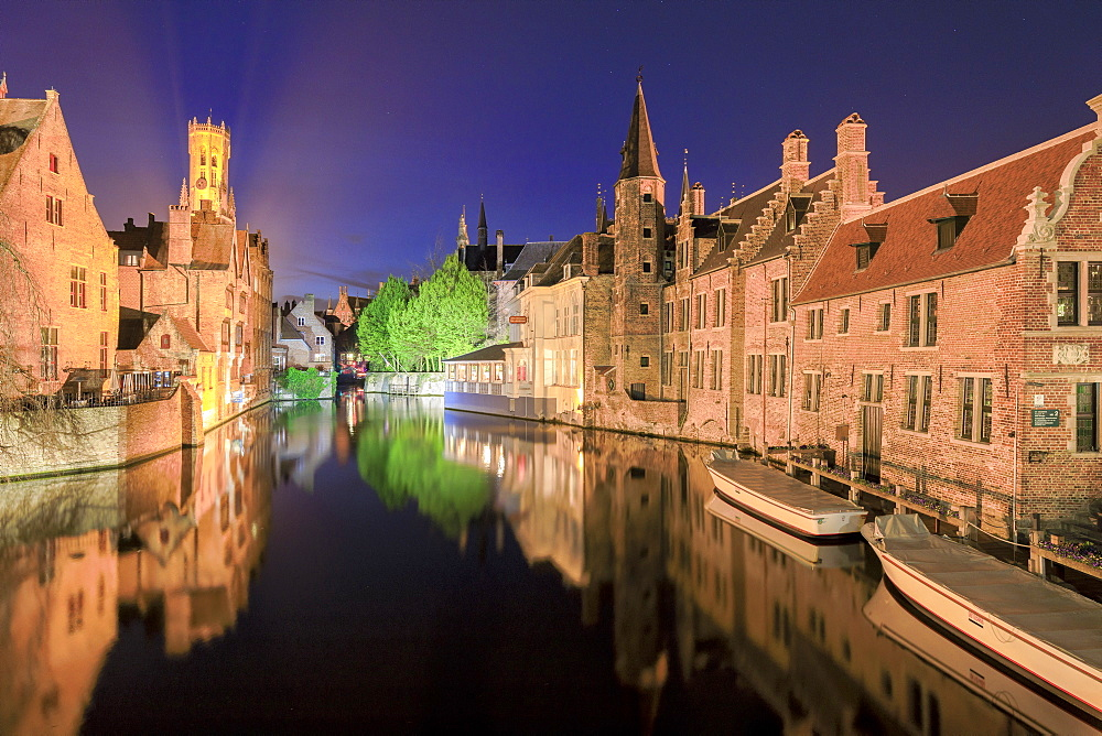 The medieval Belfry and historic buildings are reflected in Rozenhoedkaai canal at night Bruges West Flanders Belgium Europe