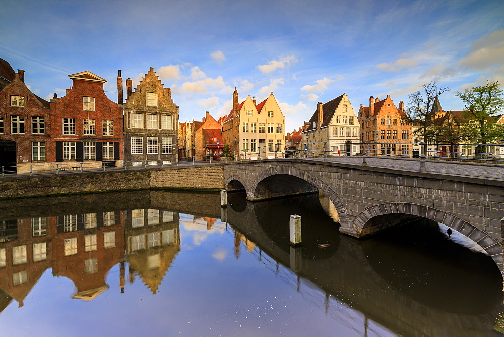 First lights of sunrise on the historic buildings and bridge reflected in the typical canal Bruges West Flanders Belgium Europe