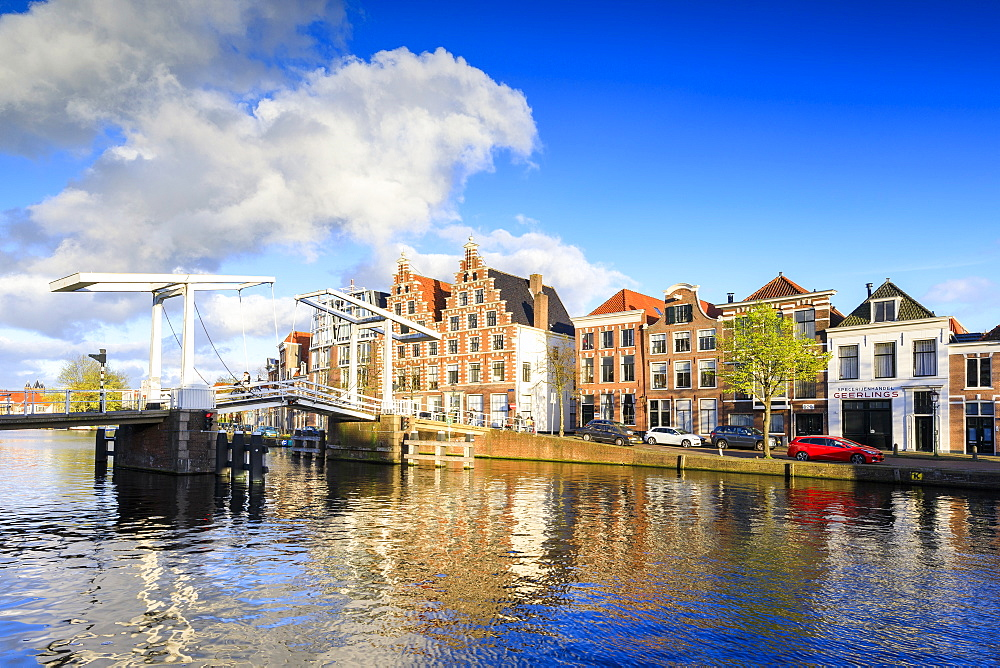 Blue sky and clouds on typical houses reflected in the canal of the River Spaarne, Haarlem, North Holland, The Netherlands, Europe