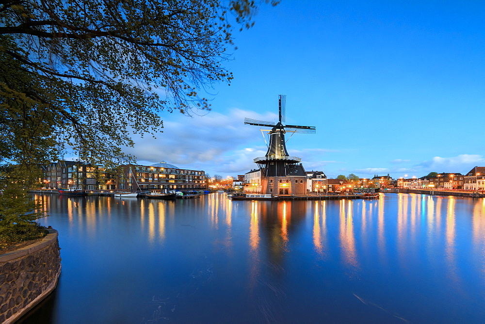 Dusk lights on the Windmill De Adriaan reflected in the River Spaarne, Haarlem, North Holland, The Netherlands, Europe