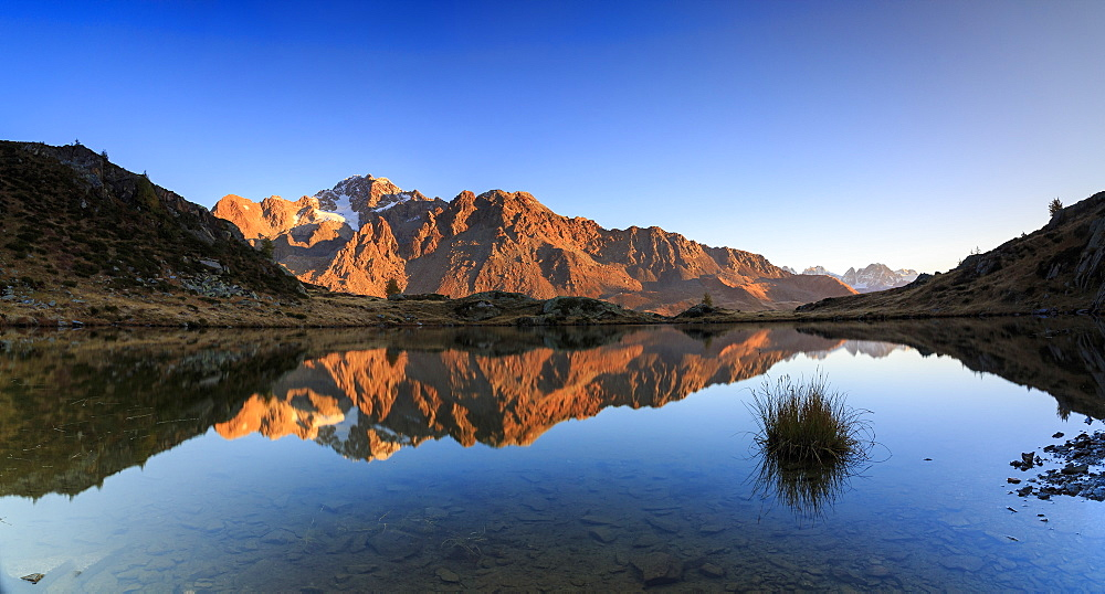 Panorama of the rocky peaks of Mount Disgrazia reflected in Lake Zana at dawn, Malenco Valley, Valtellina, Lombardy, Italy, Europe