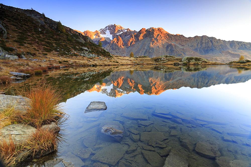 Rocky peaks of Mount Disgrazia reflected in Lake Zana at sunrise, Malenco Valley, Valtellina, Lombardy, Italy, Europe - 1179-2233