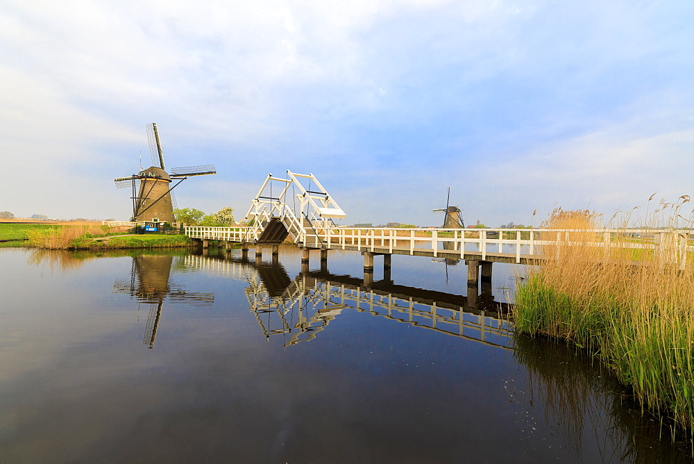 Traditional windmills and bridge on the canal framed by sunrise, Kinderdijk, UNESCO World Heritage Site, Molenwaard, South Holland, The Netherlands, Europe