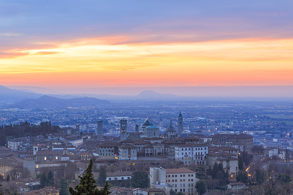 View of the medieval old town called Citta Alta (Upper City) on hilltop framed by the fiery orange sky at dawn, Bergamo, Lombardy, Italy, Europe - 1179-2258
