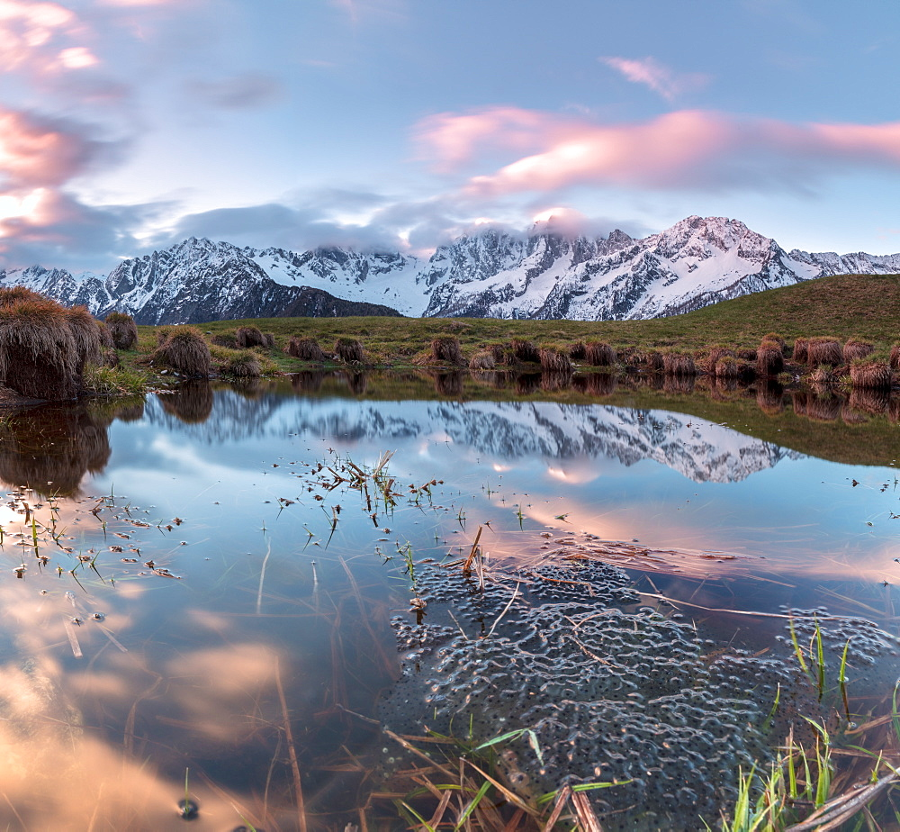 Panorama of pink clouds reflected in water at dawn Tombal Soglio Bregaglia Valley canton of Graubünden Switzerland Europe